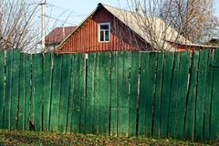 Part of an old rural fence of green wooden boards on the street. Part of the old long rural fence of green wooden boards on the street stock images