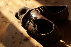 Part of old shoes with laces on wooden floor. Part of old dirty brown leather shoes - space for copy and text Stock Photos