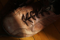 Part of old shoes with laces on wooden floor. Part of old dirty brown leather shoes - space for copy and text Stock Image