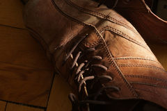 Part of old shoes with laces on wooden floor Royalty Free Stock Image