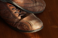 Part of old shoes with laces on wooden floor Stock Image