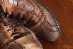 Part of old shoes with laces on wooden floor Stock Photography
