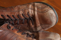 Part of old shoes with laces on wooden floor. Part of old dirty brown leather shoes - space for copy and text Stock Photo