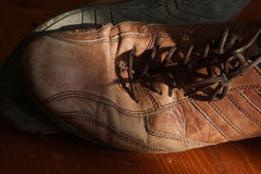 Part of old shoes with laces on wooden floor. Part of old dirty brown leather shoes - space for copy and text Stock Images