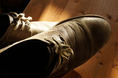 Part of old shoes with laces on wooden floor Royalty Free Stock Photos