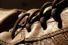 Part of old shoes with laces on wooden floor. Part of old dirty brown leather shoes - space for copy and text Royalty Free Stock Photo