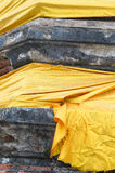 Part of old stone pagoda wrapping with a gold fabric Stock Photography