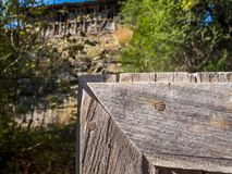 Part of an old wooden gate in the foreground, blurred old wooden barn in the background, at Debnevo, Bulgaria Royalty Free Stock Photo
