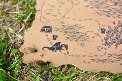 Old worlde antique style burned treasure map with dragon garding chest lying in grass stock photo