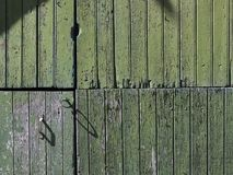 Part of old green painted barn door with vertical planks. Part of old worn down grungy green painted barn door with vertical planks Royalty Free Stock Images