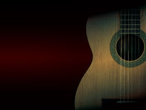 Part of a orange acoustic guitar on black background. Royalty Free Stock Images