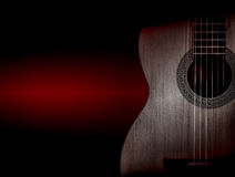 Part of a orange acoustic guitar on black background. Stock Image