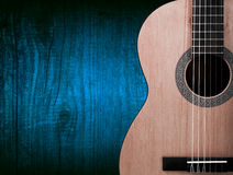 Part of a orange acoustic guitar on wooden background. Royalty Free Stock Photos