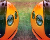 Part of an orange car on a background of grass. Orange luxury car royalty free stock photography