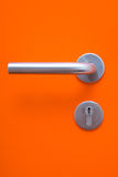 The part of orange door with metal handle. And keyhole Stock Image