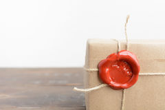 A part of parcel wrapped in craft paper with rope and red sealing wax. Over brown wooden background royalty free stock image