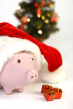 Part of piggy bank with Santa Claus hat and three little gifts and shining christmas tree standing on white background Royalty Free Stock Photos