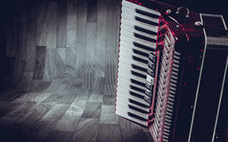 Part pink accordion on wooden grey background. Write text Royalty Free Stock Photography