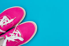Part of the Pink sneakers with white laces on a blue Stock Photo