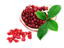 Part of pomegranate fruit with green leaves isolated on white. Royalty Free Stock Photo