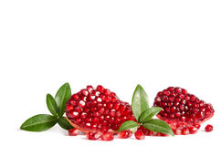 Part of a pomegranate with pomegranate seeds and leaves Stock Photos