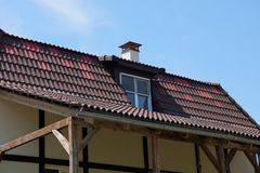 Part of a private house with a brown tiled roof and a window royalty free stock images