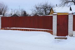 Part of a long red metal fence and a closed door in white snow outside stock photos