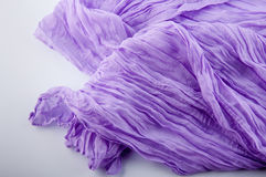 Part of purple soft wrinkled fabric on white background Stock Photos