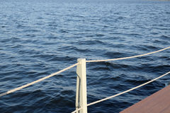 The part of the quay and the fencing with ropes from the water surface Stock Photo