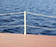 The part of the quay and the fencing with ropes from the water surface Stock Images
