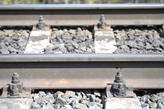 Part of the railway section close-up with rails and a concrete beam on a stone base from rubble. Sharpness on the near rail stock photo
