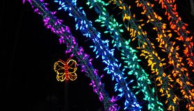 Part of rainbow and butterfly lights at Christmas light show. Beautiful holiday lights on this colorful rainbow with a butterfly flying next to it stock photos
