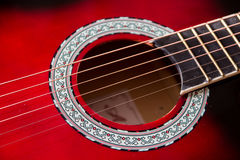 Part of red acoustic guitar. Close up.  Royalty Free Stock Photos