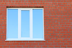 Part of red brick wall and blue window with double glazing Stock Photo