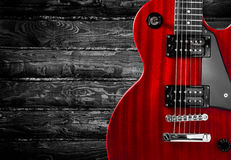 Part of the red electric guitar on wooden background. A place for writing of the text. Royalty Free Stock Photo