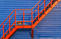 Part of red fire escape on the blue wall Stock Photo