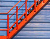 Part of red fire escape on the blue wall Royalty Free Stock Image