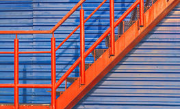 Part of red fire escape on the blue wall Stock Photography