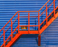 Part of red fire escape on the blue wall Stock Images