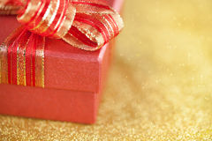 Part of red gift box on glitter gold background Stock Image