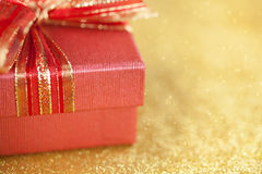 Part of red gift box on glitter gold background. Royalty Free Stock Images