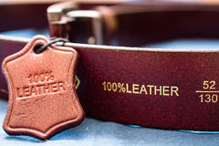 Part of red leather belt. Natural material label with caption Royalty Free Stock Photos