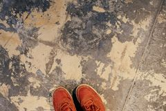 Part of red sneakers on the surface of the old plaster floor. stock photography