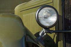 Part of the retro car closeup khaki color. Forward part of the retro military car with a headlight closeup of khaki color Stock Photos