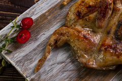 Part of roasted quail. Part of roasted quail with spices on a wooden background Stock Photo