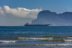 The rock of Gibraltar and a cargo ship royalty free stock image