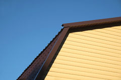 Part of rural house Wall covered with yellow siding and brown metal roof front view Royalty Free Stock Images