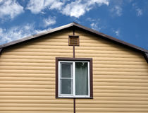 Part of rural house wall covered with yellow siding and brown metal roof front view Royalty Free Stock Photography