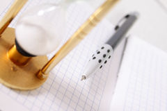 Part of a sand-glass on notebook with the pen Stock Photo