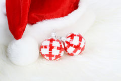 Part of Santa Claus hat with pom-pom and two red and white Christmas balls. On white fur Royalty Free Stock Photo